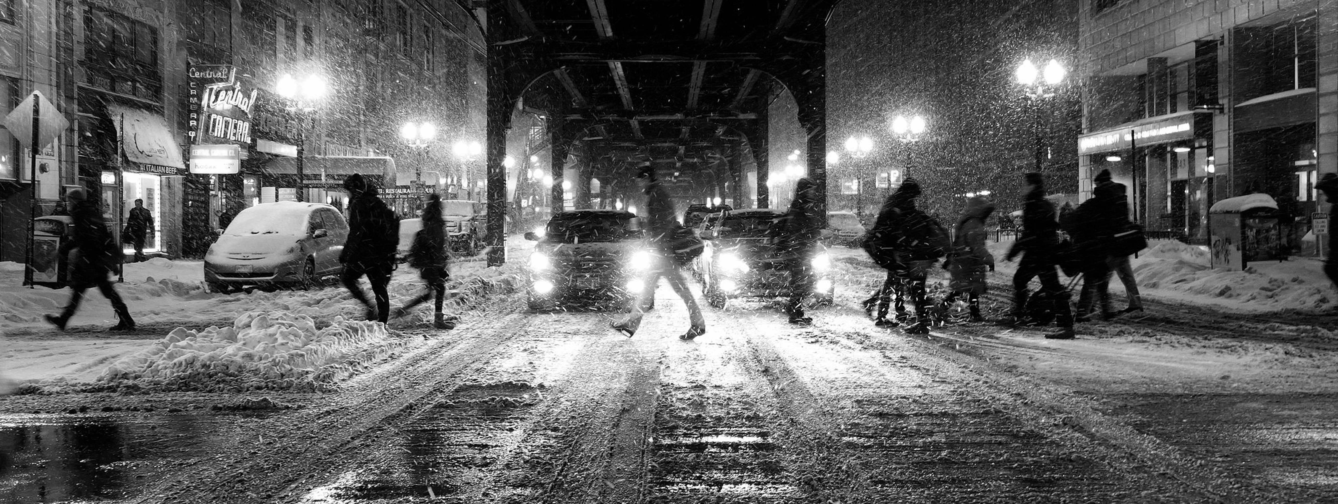 black and white photo of people crossing the street while it's snowing